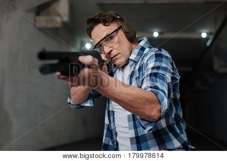 One shot. Confident skilled nice shooter holding the gun and pulling the trigger while shooting