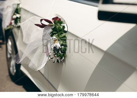 Close-up Of Floral Wreath On Car Door, Wedding Ceremony Vehicle, White Daisies With Red Ribbon On We
