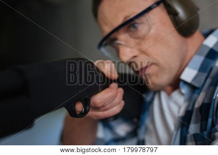 Time to fire. Serious determined nice man wearing protective ammunition and holding a gun while pulling the trigger