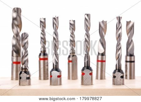 drill bits for wood standing on wooden stand on a white background