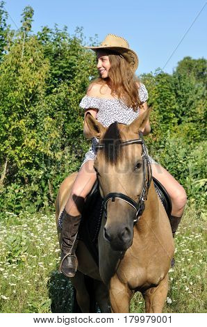 teenage girl horseback riding in the summer sunny day