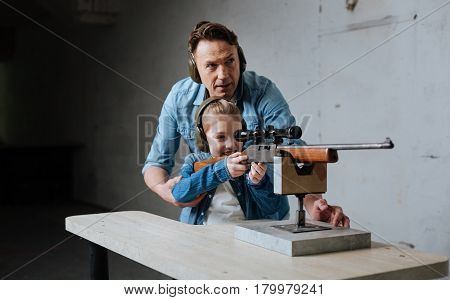 Interesting experience. Nice cute cheerful girl holding a gun and learning how to use it while being assisted by her father