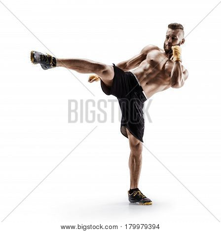 Athletic man practicing tae-bo exercises kicking forward with legs. Photo of sporty muscular male in sports clothes over white background