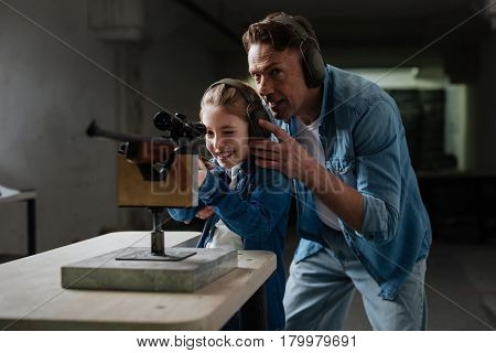 Care and support. Pleasant supportive joyful father standing behind his daughter and giving advice to her while having a shooting lesson with her