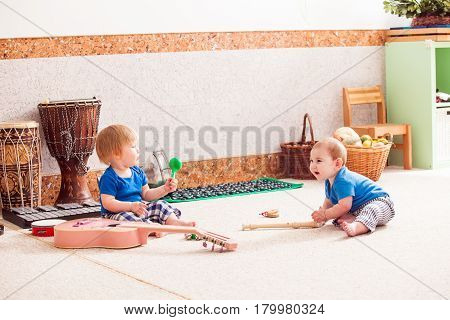 Two little boys enthusiastically playing with various musical instruments