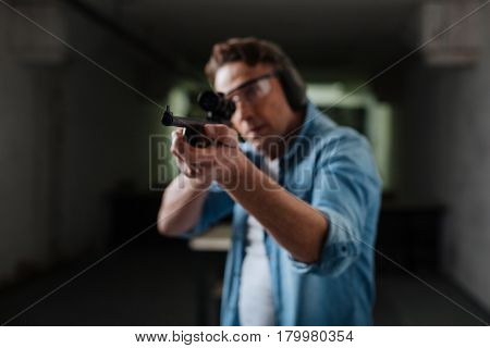 Pneumatic weapon. Serious brutal nice man holding the rifle and firing while trying to hit the target