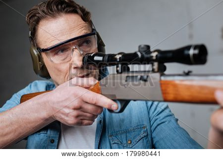 Perfect skills. Skilled professional marksman holding a gun and preparing to shoot while having target practice