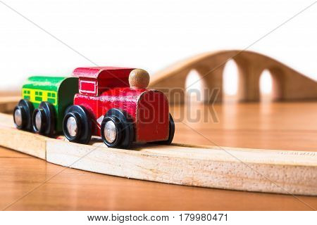 Toy Train Made Of Wood With Bridge In Backdrop