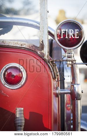 FIRE written on a red light on the side of an old, antique red fire truck.