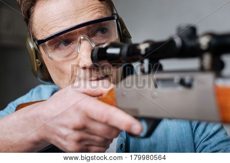 Protective equipment. Good looking handsome pleasant ma wearing safety glasses and aiming with his gun while visiting a shooting gallery