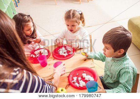 A group of children in kindergarten sitting at a wooden table and eating rice
