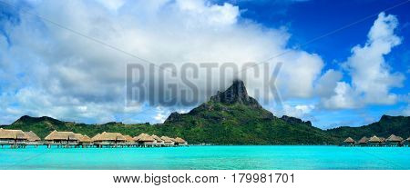 Panorama image of a tropical Bora Bora landscape with green Otemanu mountain behind a luxury resort in the turquoise lagoon of the island near Tahiti in Pacific French Polynesia.
