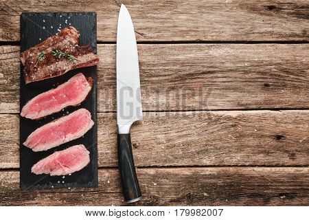 Slices of superior grilled meat on black slate with big knife on rustic wooden table, copy space for text. Kitchen, cooking, restaurant serving concept