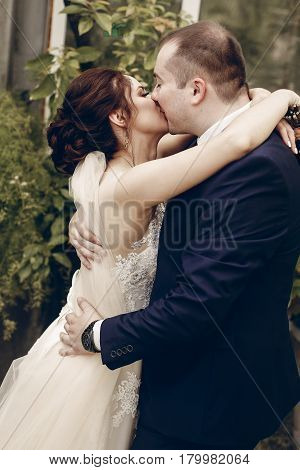 Happy Newlywed Couple Kissing Outdoors After Ceremony, Handsome Groom Embracing Brunette Bride In A