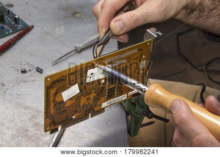 Repair of computer hardware. Modem repair. Replacement of the capacitor.Hand of a soldering soldier with soldering iron.