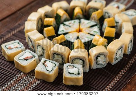 Delicious colorful tasty set of sushi rolls served on straw mat, closeup. Japanese luxury restaurant menu photo, traditional seafood.