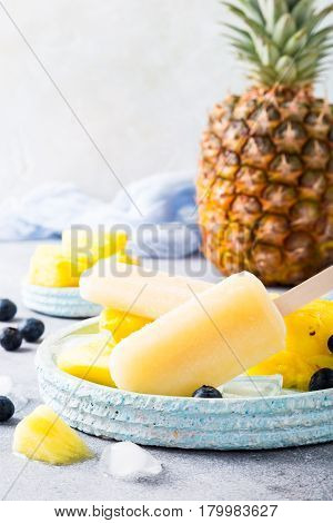 Fresh frozen juice ice cream, pineapple popsicles with blueberries on light blue plate. Summer food concept.