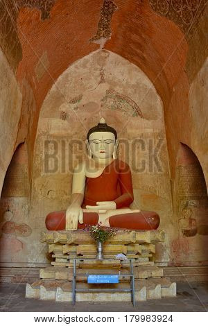 Very Old Buddha Sculpture Inside Pagoda In Bagan, Myanmar. Ancient Frescos On The Walls Of Pagoda.