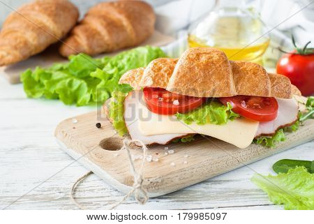 Croissant sandwich with bacon cheese lettuce and tomato on white wooden table. Healthy snack.