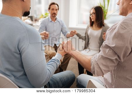 It is teambuilding. Relaxed coworkers holding hands being in conference hall while doing consolidating tasks