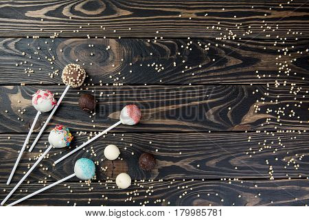 colorful cake pops set on wooden background for text. celebration cake pops on tabe for text typing.