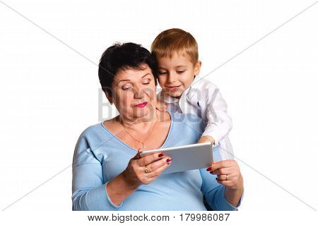 Grandmother with her small grandson use a tablet on a white background