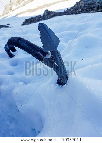 Closeup of ice axe on steep slope. Ascending snow covered mountaint.