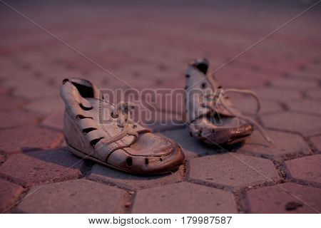Old worn baby shoes on the sidewalk tile. The concept of poverty