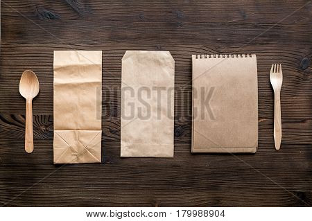 breakfast take away with flatware and paper bags on wooden table background top view