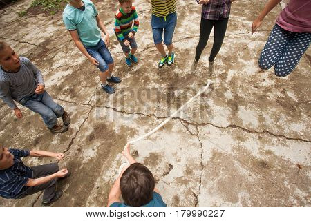 Children play outdoors jumping over the rope