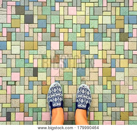 Colorful bricks background and female feet. Woman's legs in white and blue textile shoes. Comfort shoes for travel. Street style footwear for women. Foot on pathway banner template with text place