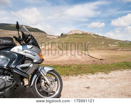 Italy Castelluccio di Norcia - april 24 2015: Motocicle parked on the big plan of Monti Sibillini. The motorcycle is located on the roadside overlooking the floor dedicated to the cultivation of lentils