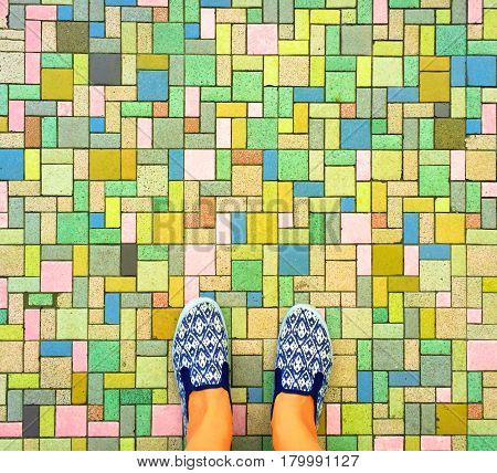 Colorful bricks background and female feet. Woman's legs in white and blue textile shoes. Comfort shoes for travel. Street style fashion photo. Tiled pathway and feet. Walking outdoor banner template