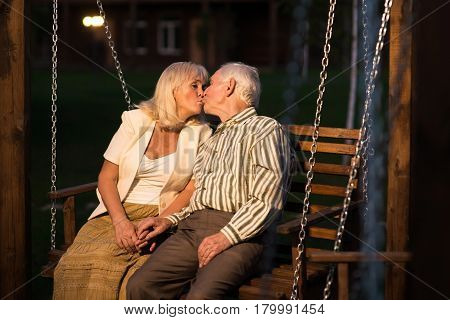 Couple on porch swing kissing. Man and woman outdoors, evening. How to find love.
