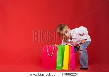 Little boy peers into his packages with gifts on a red background