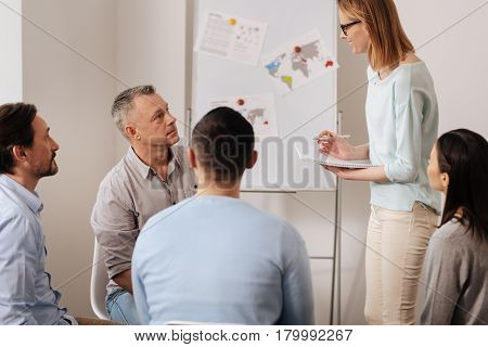 Look and smile. Attractive blonde standing in semi position listening attentively to her coworkers, while making some notes