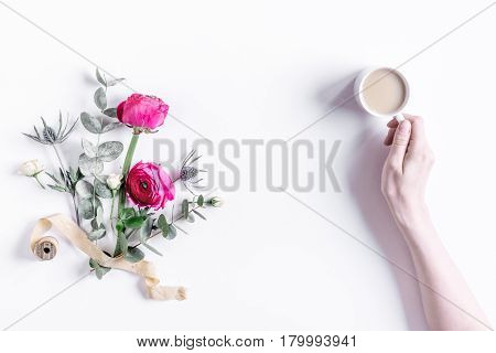 Modern spring design with bright pink flowers and coffee in hand on white desk background top view moke up