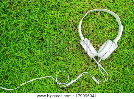 White headphones on green grass. Summer lawn with personal device. Listen to music concept photo. Spring grass with white earphones flat lay. Hipster retro headphones banner template with text place
