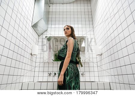 Portrait of cute young woman standing in water closet