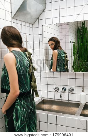 Beautiful young woman standing and looking at the mirror in water closet