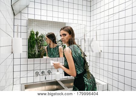 Pretty young woman standing and washing hands in water closet