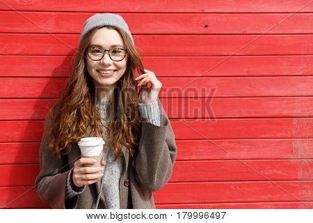 Cheerful cute young woman in hat and glasses drinking take away coffee over red wall background
