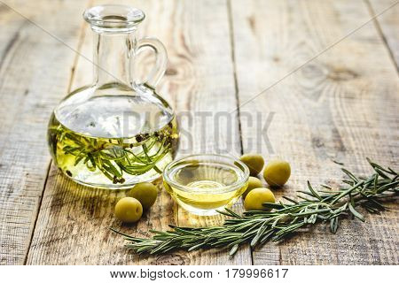extra oil in carafe with spices and fresh olive on wooden desk background mock-up