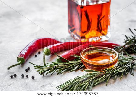 extra oil in carafe with spices and fresh chili on stone desk background