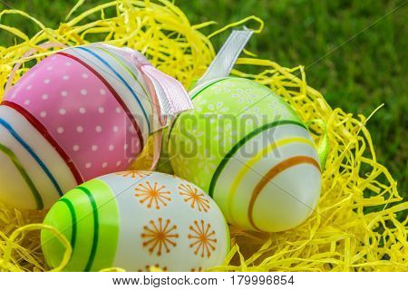 painted decorated Easter eggs on yellow straw and spring grass