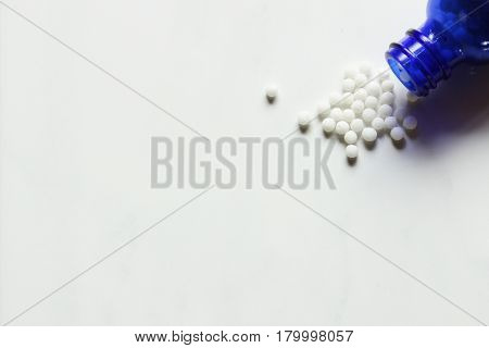 Homeopathic remedy spills from blue glass bottle. White copy space.