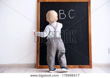 Cute little boy writing on blackboard in classroom