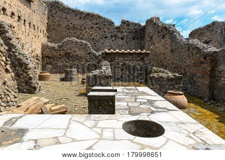 Ruins of an ancient bar (thermopolium) in Pompeii, Italy. Pompeii is an ancient Roman city died from the eruption of Mount Vesuvius in 79 AD.