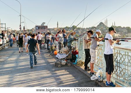 ISTANBUL - MAY 26: Fishermen and tourists are on the Galata Bridge on may 26, 2013 in Istanbul, Turkey. The Galata Bridge is one of the main attractions of Istanbul.