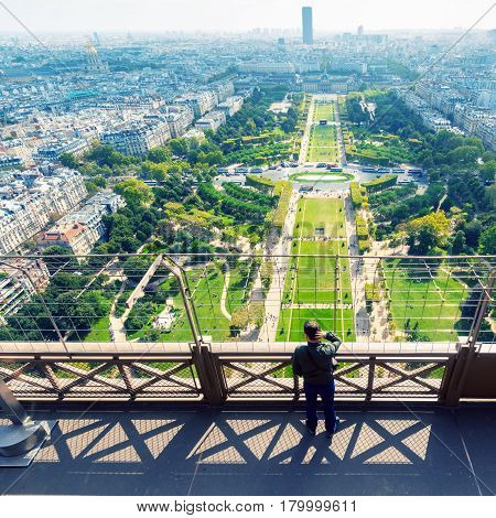 PARIS - SEPTEMBER 20, 2013: Tourist looking to the Champ de Mars on the observation deck of the Eiffel Tower in Paris. The Eiffel tower is one of the major tourist attractions of France.